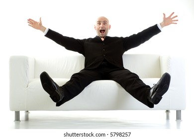 Man in a black suit sitting on a white couch, with his arms and legs stretched out in the air and a look of surprise on his face.  Isolated on white background.