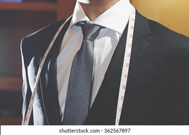 man in black suit with tie and measure tape.