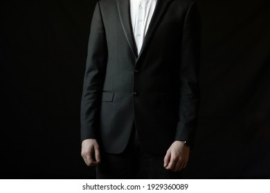 A man in a black suit and white shirt on a black background. Businessman in the dark. Male style.