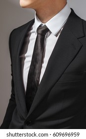 A man in a black suit and a white shirt with a black tie