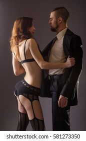 A man in a black suit and a woman in lingerie, on a gray background photo. Passionate woman in stockings takes off his jacket with men