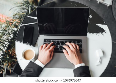 A man in a black suit works with a laptop and coffee, close-up