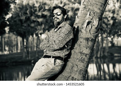 Man in a black sunglass standing with a parts of tree unique photo