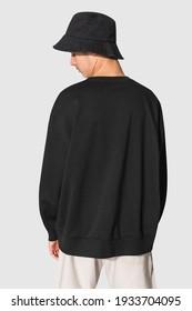 Man in black sweater and black bucket hat teen's apparel shoot