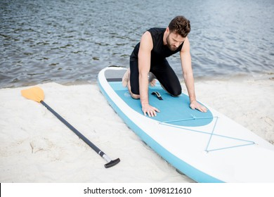 Man in black swimwear learning to keep balance on the standup paddleboard on the beach