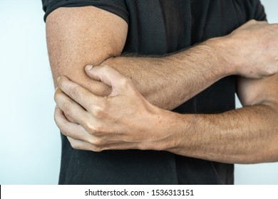 man with black t shirt and hand on elbow, injury concept
