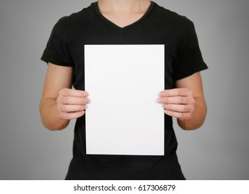 Man in black t shirt holding blank white A4 paper. Leaflet presentation. Pamphlet hold hands. Man show clear offset paper. Sheet template. Isolated on grey background.