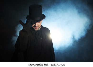 Man in a black top hat and cloak. Demonic image. Magician illusionist. Smoke background
