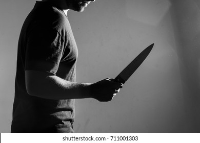 Man in black t-shirt, standing holding a knife. Indoors. Converted to black and white, grain added.