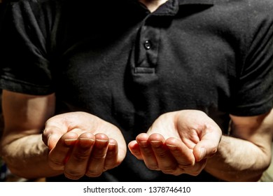 A man in a black t-shirt stands with outstretched hands