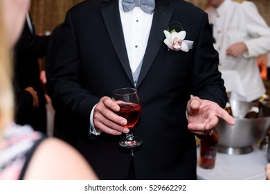 Man in black tuxedo holds glass of red wine