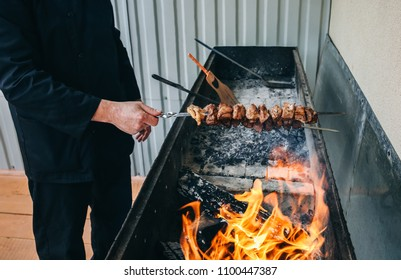 Man in black uniform is frying meat pork on the grill.  Cook is making shish kebab for summer party. Shashlik on wooden panels and open fire.