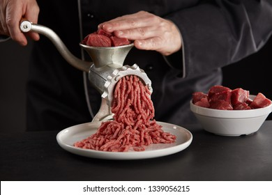 Man in black uniform making minced meat of beef or pork with old metal manual grinder. Pieces of fresh red meat for mincing in white bowl. Process of preparing meat for meatballs, viewed in close-up