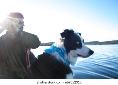 Man and black and white dog in canoe with water in background