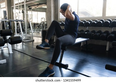 Man in Black workout cloth situp on bench in Gym Fitness shop in cool vintage tone