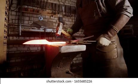 A man blacksmith forging a hot knife blade using a hammer