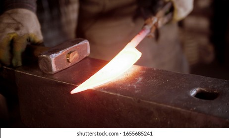 A man blacksmith forging a hot knife blade with a hammer