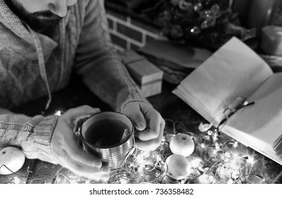 a man with a blank book in his hands for the New Year's table with decorations
