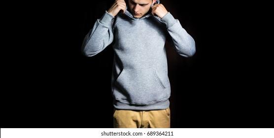 man  in the blank grey hoodie, sweatshirt on a black background, mock up, free space