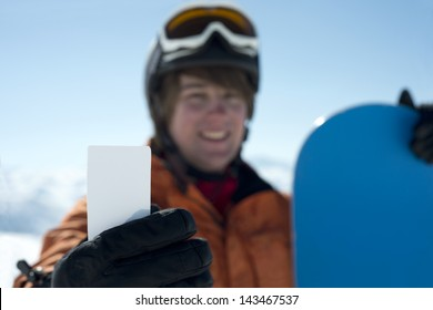 Man with blank lift pass and snowboard smiling. Concept to illustrate ski admission fee