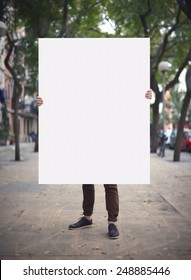 Man with blank poster on a street