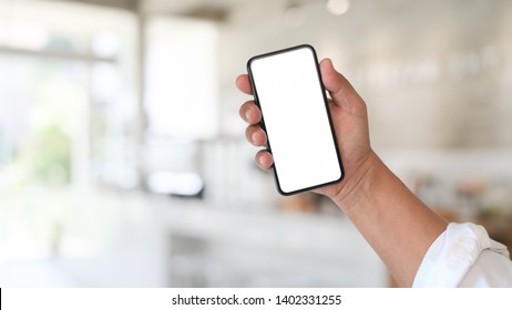 Man and blank screen mobile phone over blurred background