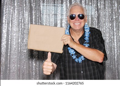 man with blank sign. A Man in a Photo Booth with a Blank Sign. Room for text. Silver sequin background photo booth.