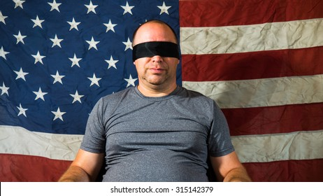Man blindfolded in front of American flag