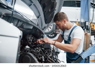 Man with blond hair. Employee in the blue colored uniform works in the automobile salon.