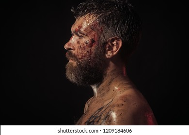 Man with bloody beard on brutal face profile. Bearded hipster with tattoo on chest on black background. Magic, enchantment, witchcraft. Wizard, sorcerer, warlock. Halloween holidays, copy space