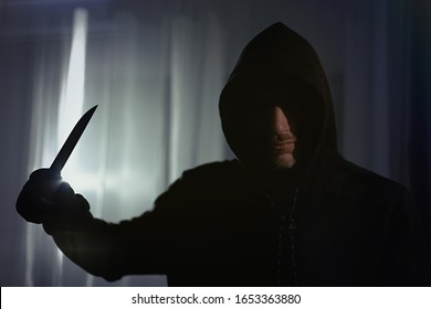A man with a bloody knife standing in apartment, hands leather gloves, armed robbery, ruthless assassin