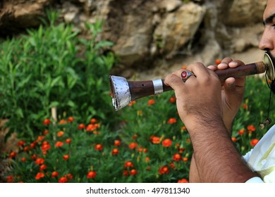A man blowing an Arabic musical wind instrument used traditionally for Dabke dance.