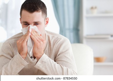 Man blowing his nose in his living room
