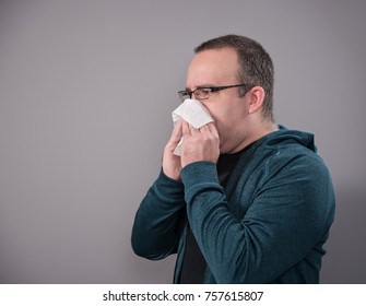 A man blowing his nose with a tissue, shot on a grey background with room for your text.