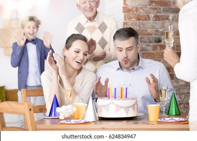 Man blowing out candles on his birthday cake