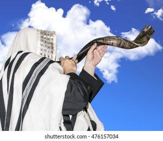 Man blowing Shofar horn for the Jewish New Year holiday (Rosh Hashanah)/Shofar to the sky/ Man blowing Shofar horn for the Jewish New Year holiday (Rosh Hashanah)