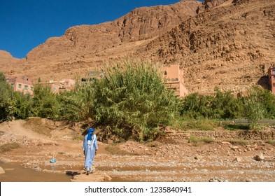 Man in Blue Berber Clothing walks in Moroccan Desert