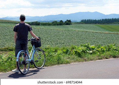 Man with blue bicycle looking out at fields