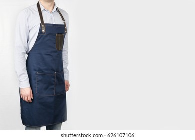 A man in a blue Chef apron on a gray background.
