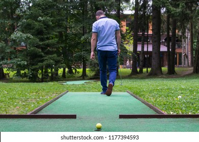 a man in blue clothes goes to the place of impact for playing mini-golf