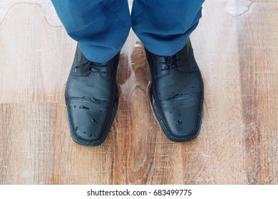 Man in blue costume pants and black shoes is standing in the water puddle on the floor