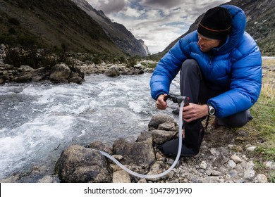 man in blue down jacket filtering water for drinking from a river in the Andes in Peru