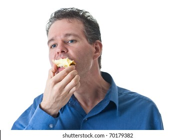 A man in a blue dress shirt, finishing off an apple, isolated on white.