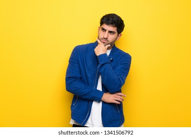 Man with blue jacket over yellow wall thinking