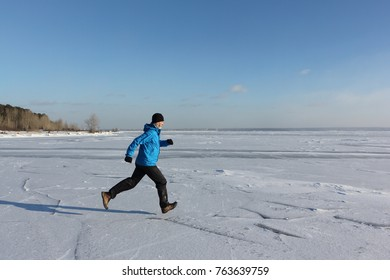 Man in a blue jacket running across the ice of a frozen river, Ob Reservoir, Russia