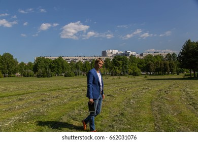 A man in a blue jacket with a tablet in the park