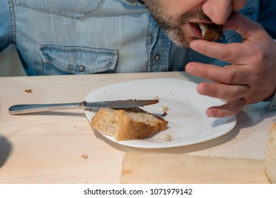 man in blue jeans shirt eating chocolate hazelnut cream on a slice of wholegrain bread on kitchen table top with a knife and slice of bread on cutting board