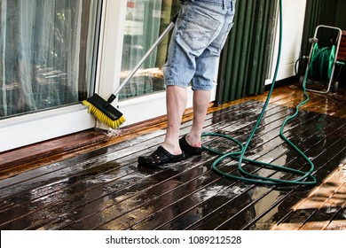 A man with blue jeans shorts is spring cleaning the window and front porch of a house with a broom, water and soap