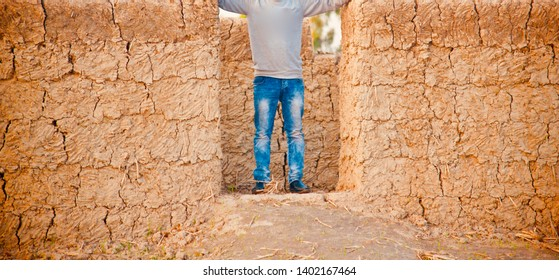 Man in blue jeans standing around a door of an incomplete clay made house