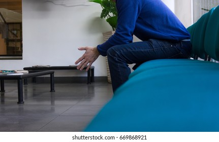 Man in blue jeans and sweater sitting on doctor's waiting room. Sickness, ill person, patience, health care delay concept
